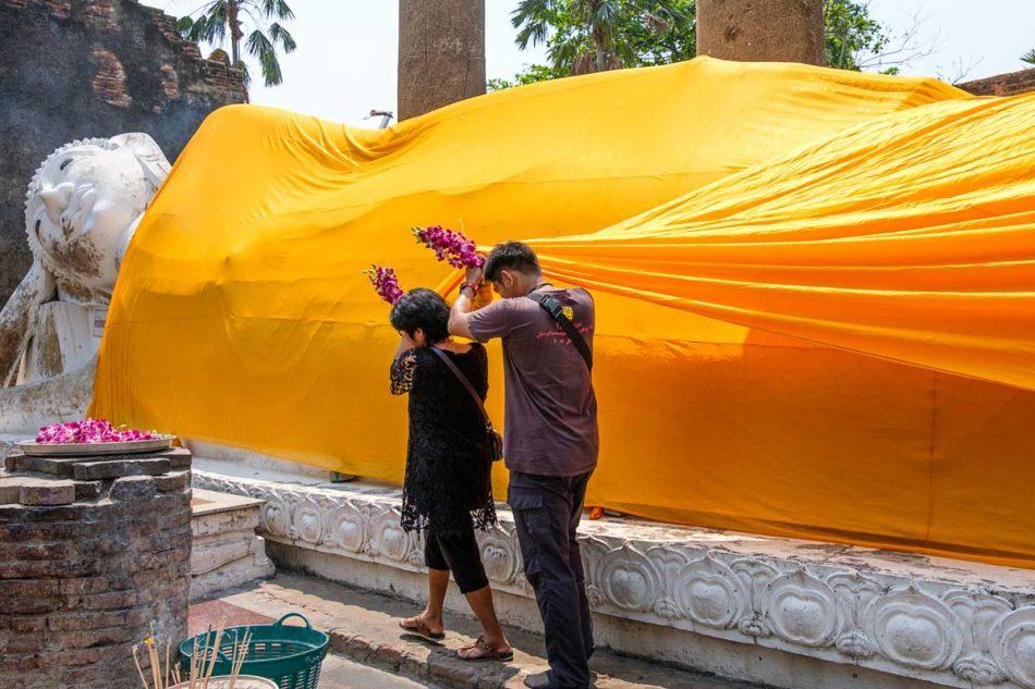 Des fidèles se livrent à toutes sortes de rituels : collage de feuilles d'or, offrandes d'encens et d'amulettes, et habillage de bouddhas dans de longs tissus jaune safran...